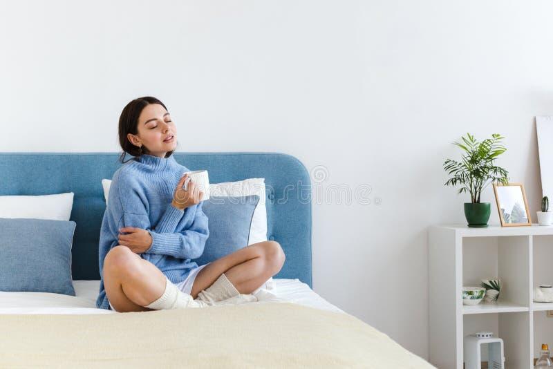 La ragazza in un maglione blu nello stile interno di Hygge con una tazza a disposizione si siede sul letto immagini stock
