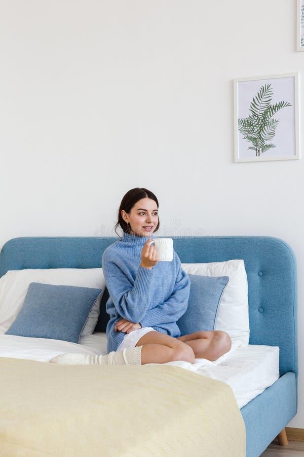 La ragazza in un maglione blu nello stile interno di Hygge con una tazza a disposizione si siede sul letto fotografia stock