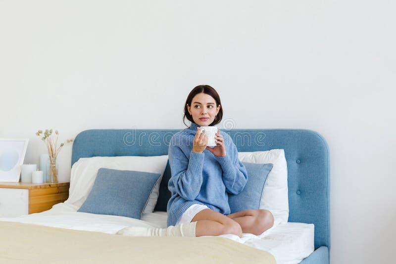 La ragazza in un maglione blu nello stile interno di Hygge con una tazza di tè caldo in sue mani si siede sul letto fotografie stock libere da diritti