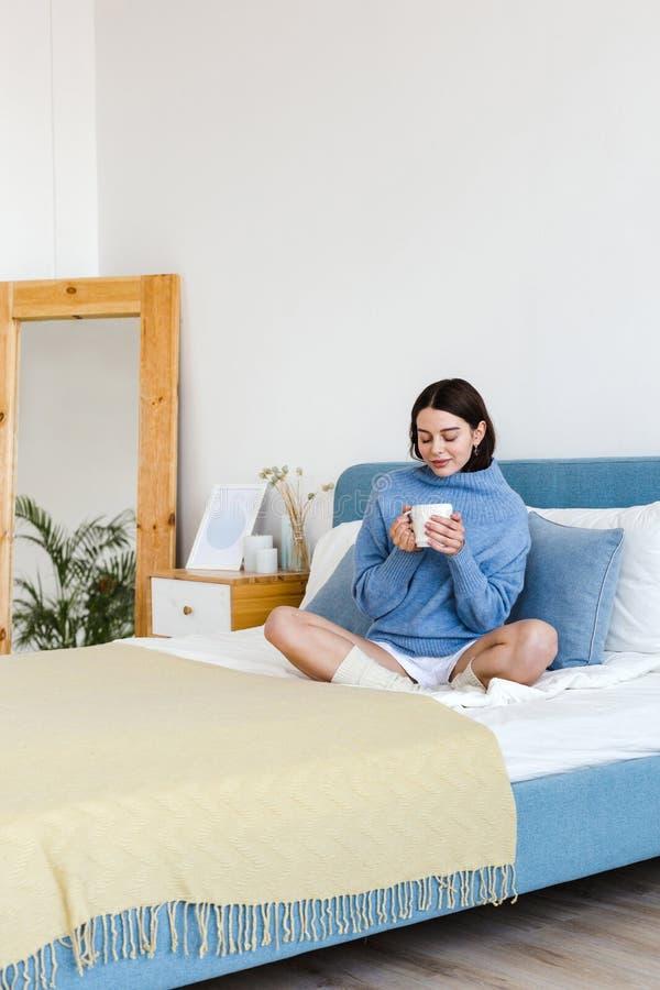 La ragazza in un maglione blu nello stile interno di Hygge con una tazza di tè caldo in sue mani si siede sul letto immagini stock libere da diritti