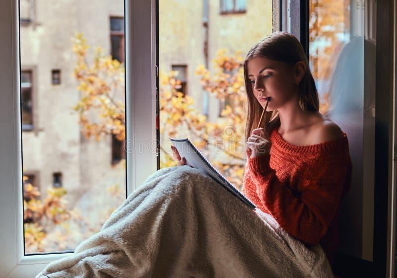 La ragazza in un maglione caldo ha riguardato le sue gambe di coperta, fa le note in suo taccuino che si siede sul davanzale dell fotografie stock libere da diritti