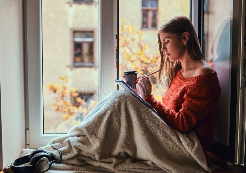 La ragazza in un maglione caldo ha riguardato le sue gambe di coperta, fa le note in suo taccuino che si siede sul davanzale dell immagine stock