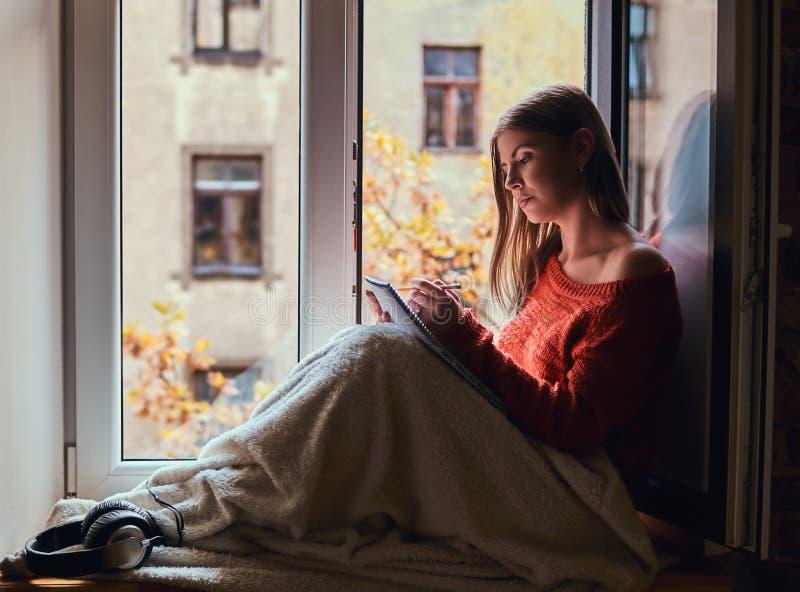 La ragazza in un maglione caldo ha riguardato le sue gambe di coperta, fa le note in suo taccuino che si siede sul davanzale dell fotografia stock libera da diritti