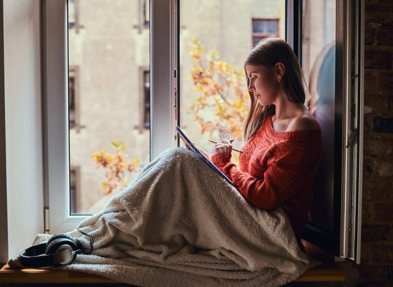 La ragazza in un maglione caldo ha riguardato le sue gambe di coperta, fa le note in suo taccuino che si siede sul davanzale dell fotografie stock