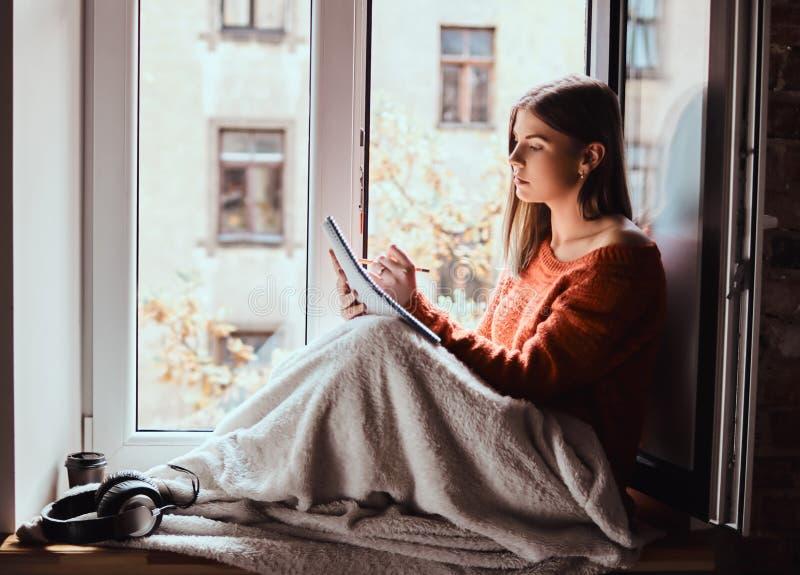 La ragazza in un maglione caldo ha riguardato le sue gambe di coperta, fa le note in suo taccuino che si siede sul davanzale dell fotografia stock