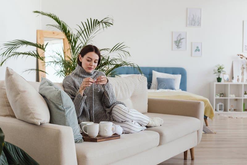La ragazza in un maglione grigio caldo tricotta la seduta su un sofà in un hygge interno accogliente fotografie stock libere da diritti