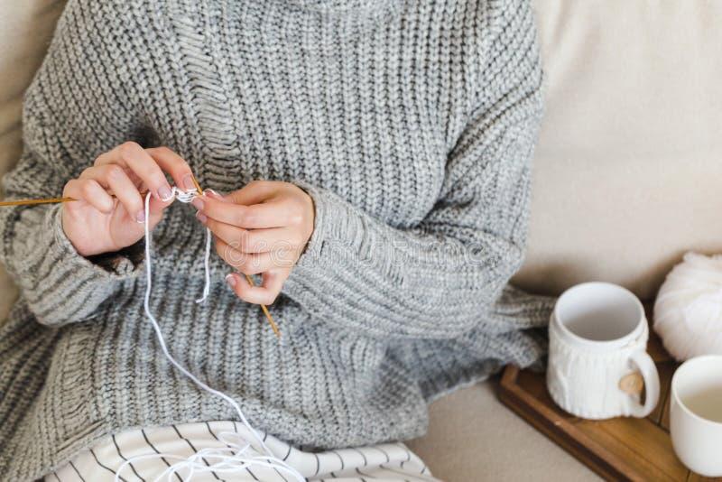 La ragazza in un maglione grigio caldo tricotta la seduta su un sofà in un hygge interno accogliente fotografia stock