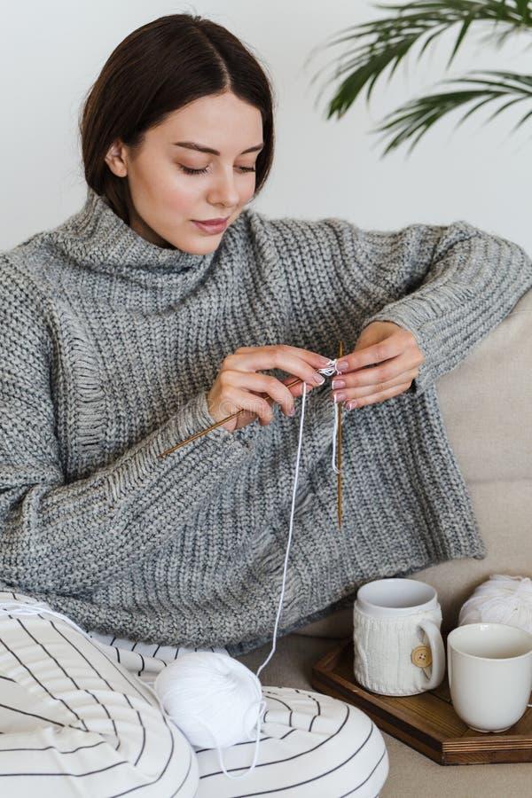 La ragazza in un maglione grigio caldo tricotta la seduta su un sofà in un hygge interno accogliente fotografia stock libera da diritti