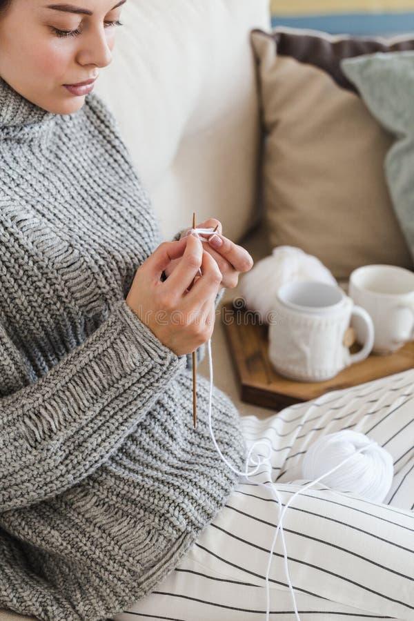 La ragazza in un maglione grigio caldo tricotta la seduta su un sofà in un hygge interno accogliente immagini stock