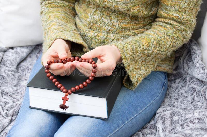 La ragazza in un maglione verde sta tenendo una bibbia e un rosario di legno con un incrocio fotografia stock
