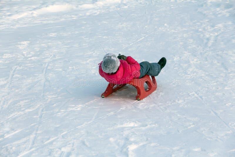 La ragazza in un rivestimento rosso guida fuori uno scorrevole della neve fotografia stock