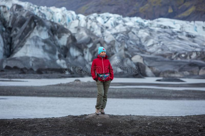 La ragazza in un rivestimento rosso sta sui precedenti di un ghiacciaio immagini stock libere da diritti