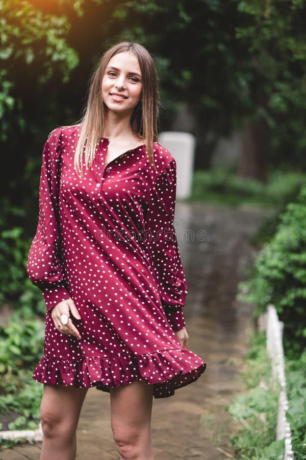 La ragazza in un vestito cremisi fotografia stock