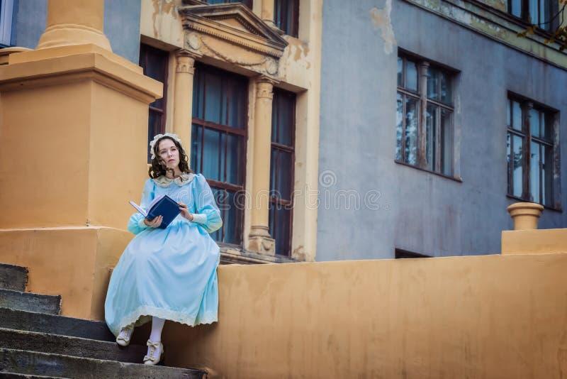 La ragazza in un vestito d'annata blu legge una storia di amore immagine stock