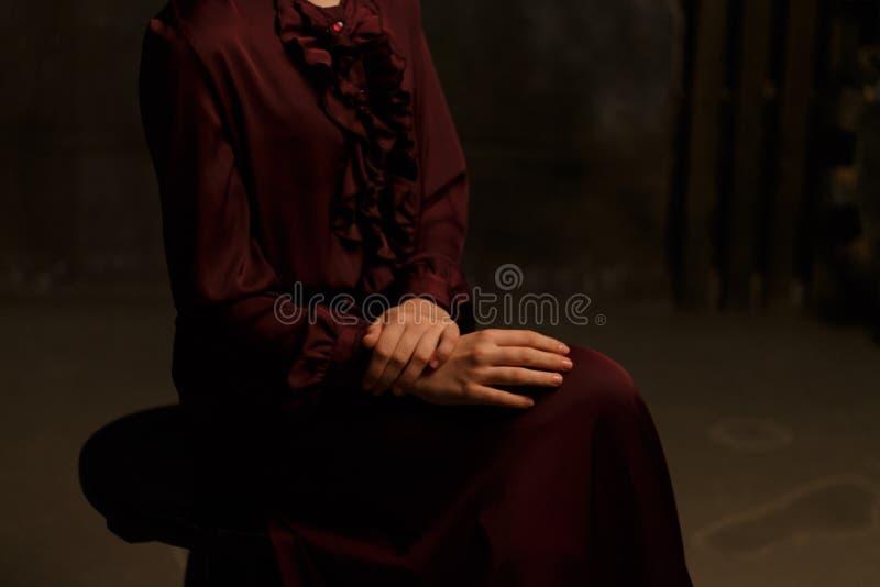 La ragazza in un vestito d'annata si siede su una sedia modesty purezza scantinato dungeon fotografia stock libera da diritti