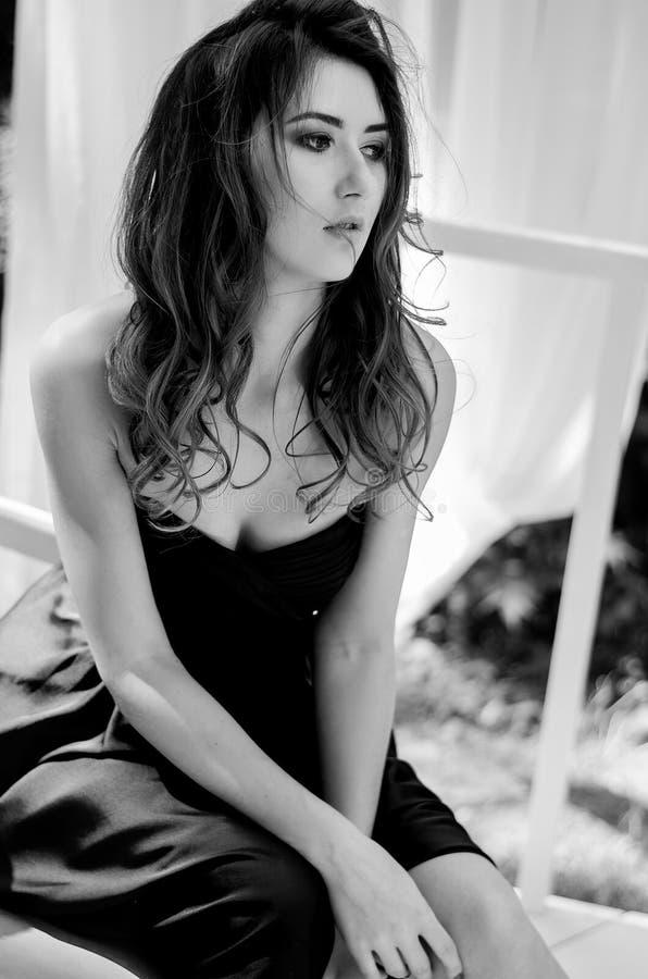 La ragazza in un vestito da sera lungo sta sedendosi su una sedia Fotographia in bianco e nero fotografia stock