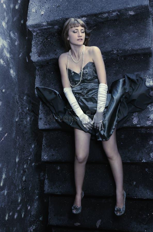 La ragazza in un vestito da sera si trova su una vecchia scala fotografie stock libere da diritti