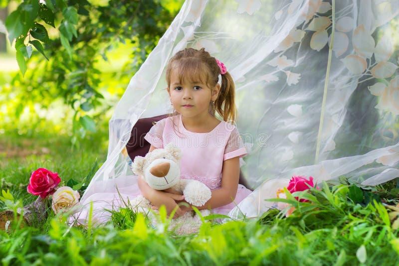 La ragazza in un vestito elegante si siede con un orsacchiotto in una tenda all'aperto fotografia stock