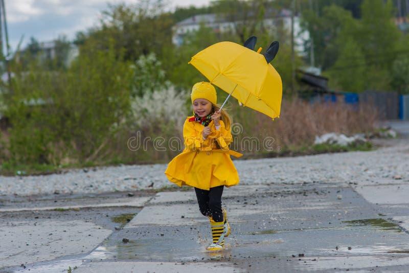 La ragazza in un vestito giallo con una molla allegra dell'ombrello passa le pozze un giorno piovoso fotografie stock libere da diritti