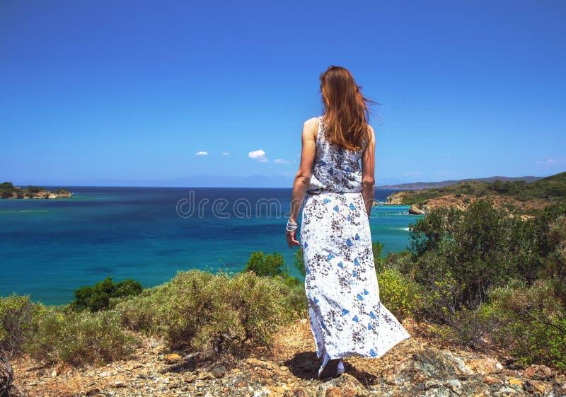 La ragazza in un vestito lungo sulla spiaggia esamina la distanza, il concetto di romanzesco, rilassamento, aspettante fotografie stock libere da diritti