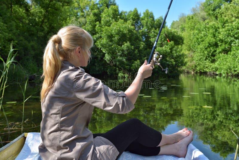 La ragazza in una barca sta pescando nel lago immagine stock libera da diritti