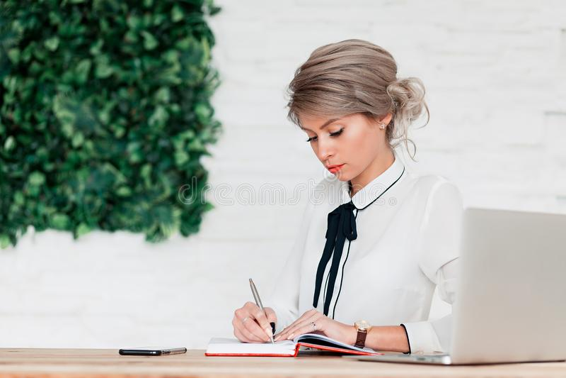 La ragazza in una blusa bianca si siede ad una tavola con un computer portatile e scrive in un taccuino rosso fotografie stock