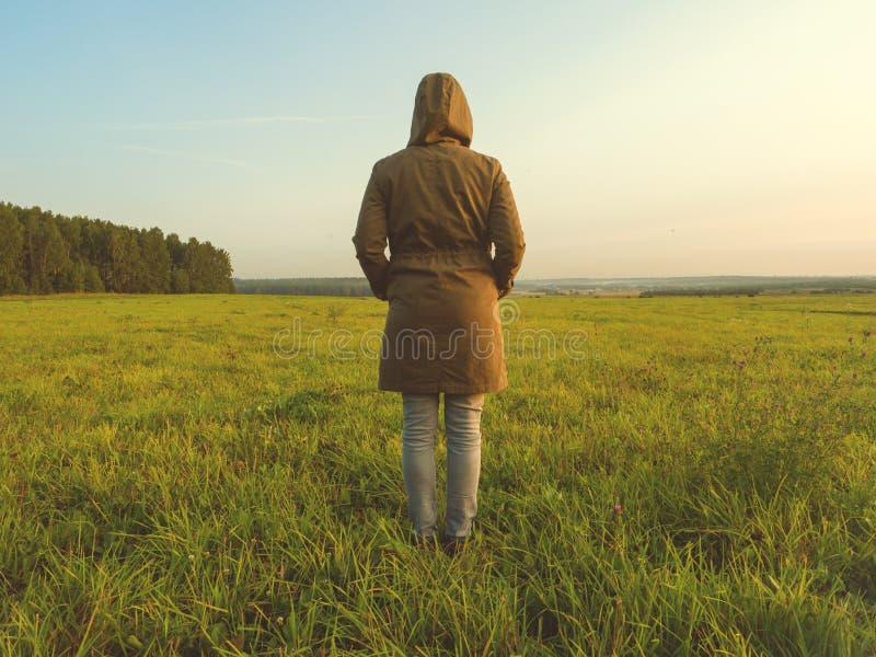 La ragazza in una giacca a vento sta indietro nel campo in autunno fotografie stock