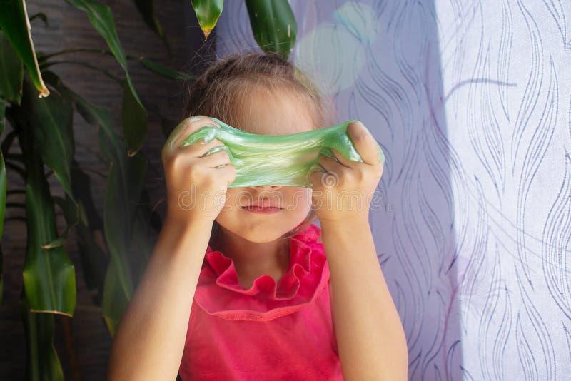 La ragazza in una maglietta rossa gioca con una melma opposta verde, la mette sopra invece di una maschera immagini stock