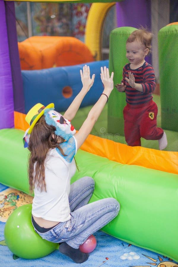 La ragazza in una maschera di un pagliaccio ai partiti dei bambini sta giocando con fotografia stock libera da diritti
