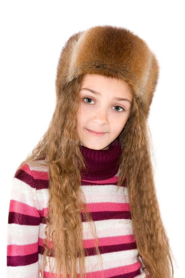 La ragazza in una pelliccia-protezione di inverno immagini stock