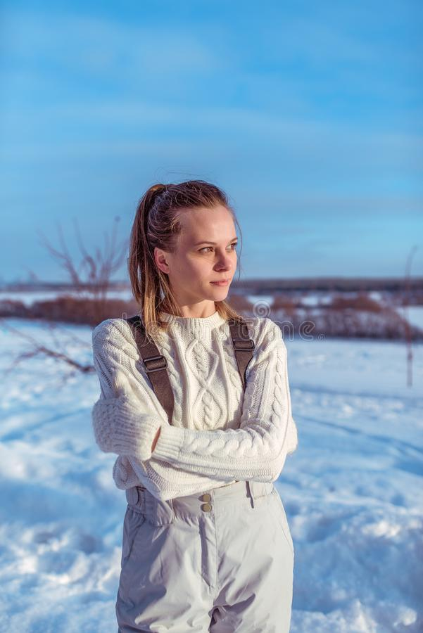 La ragazza in una tuta bianca nell'inverno fuori, fondo è derive della neve, esaminare la distanza, un maglione caldo ed il bianc fotografia stock