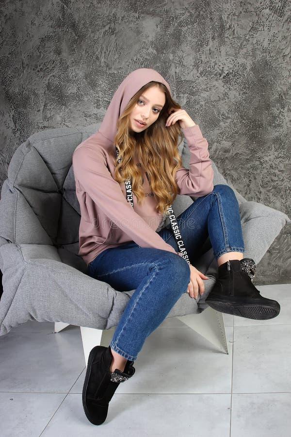 La ragazza in una tuta sportiva si siede in un interno alla moda immagine stock libera da diritti