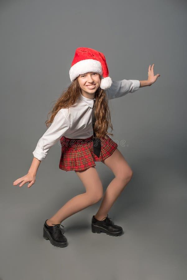 La ragazza in uniforme scolastico e cappello di Santa sta posante come surfista sul praticare il surfing immagine stock libera da diritti