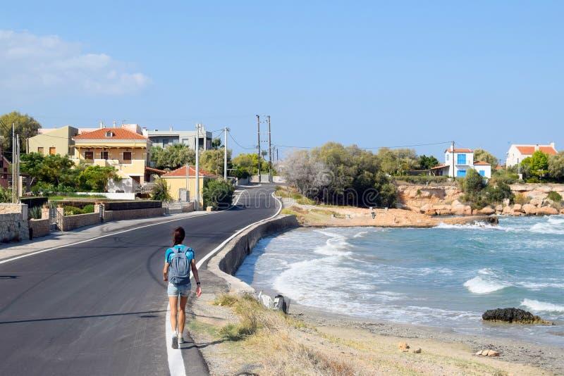 La ragazza va lungo la strada vicino alla costa di mare, la spiaggia del mar Mediterraneo sull'isola fotografie stock libere da diritti
