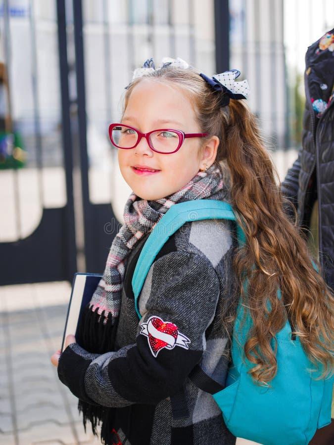 La ragazza va a scuola con una cartella e un libro immagini stock libere da diritti