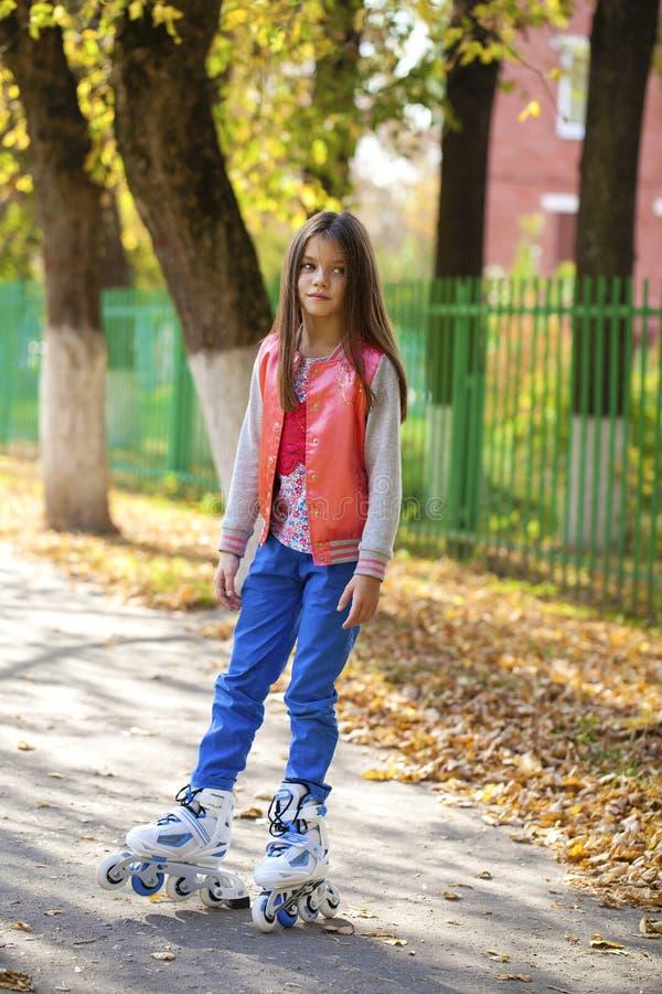La ragazza va sui pattini di rullo, all'aperto, di estate di sera fotografia stock