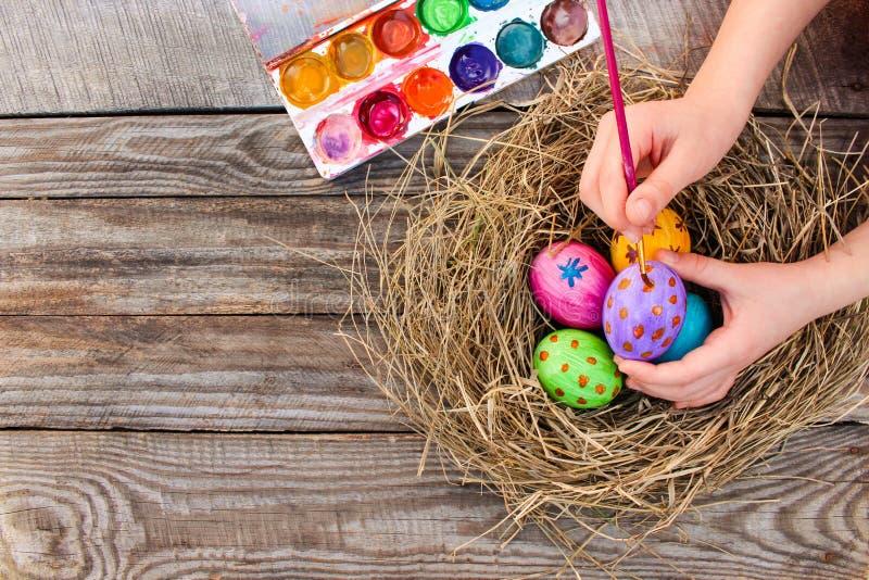La ragazza vernicia le uova di Pasqua fotografia stock