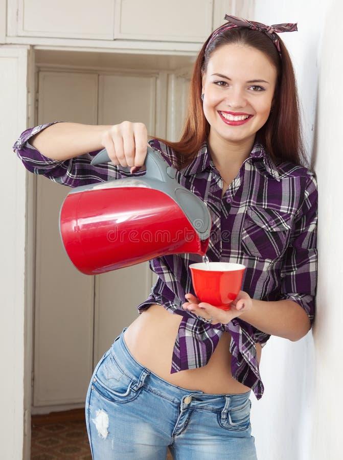 La ragazza versa l'acqua in una tazza immagini stock