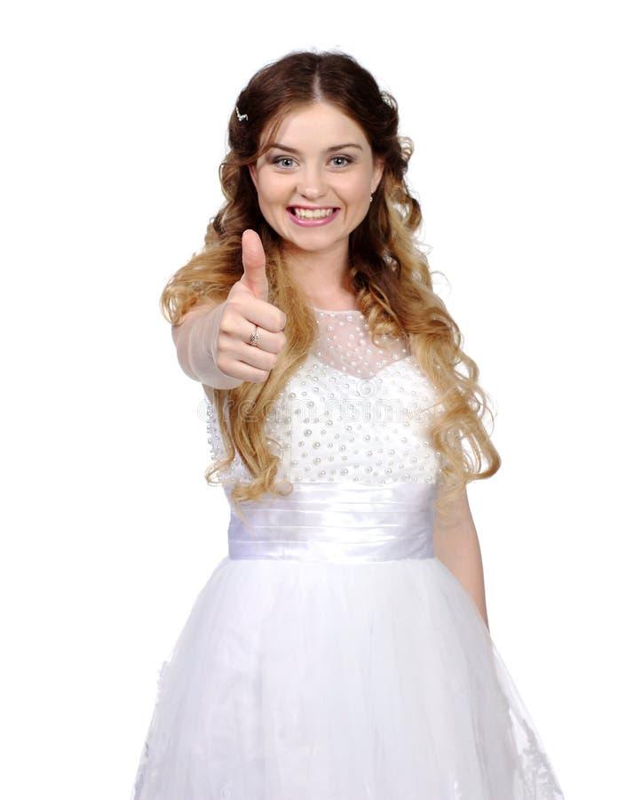 La ragazza in vestito da sposa bianco, compone i pollici immagini stock