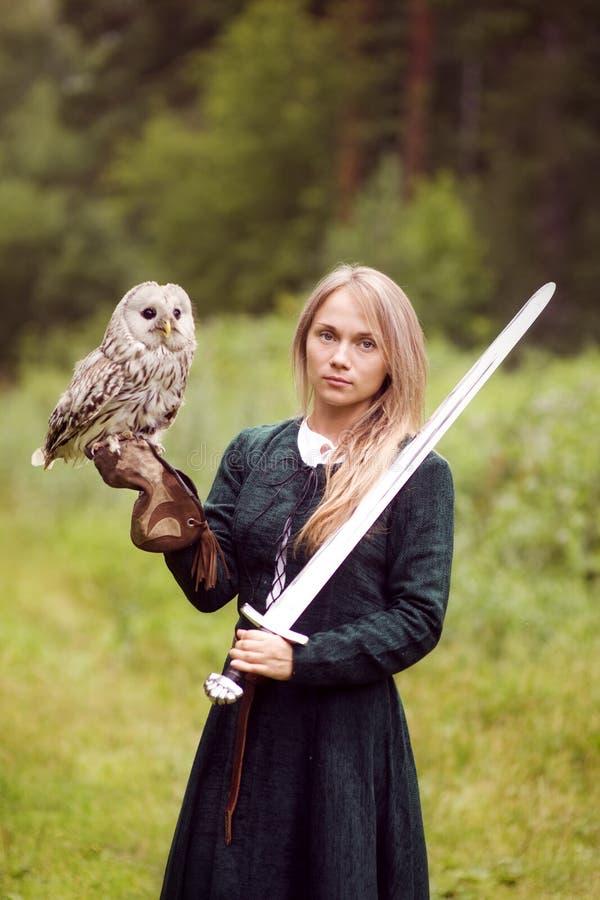 La ragazza in vestito medievale sta tenendo un gufo sul suo braccio immagine stock libera da diritti