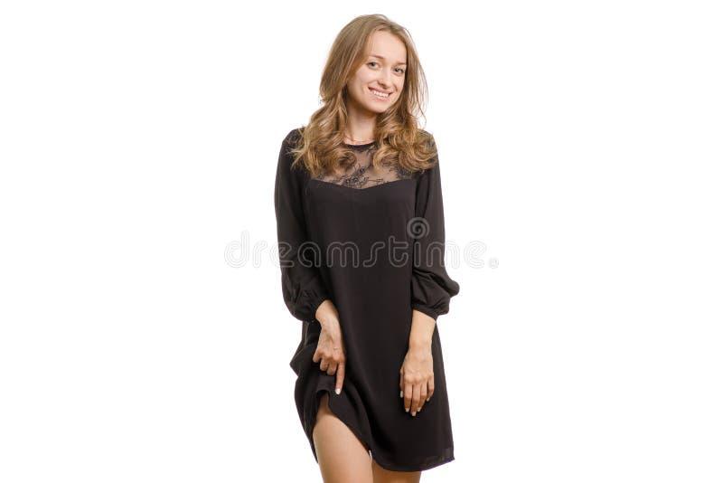 La ragazza in vestito nero alza il suo vestito fotografia stock libera da diritti