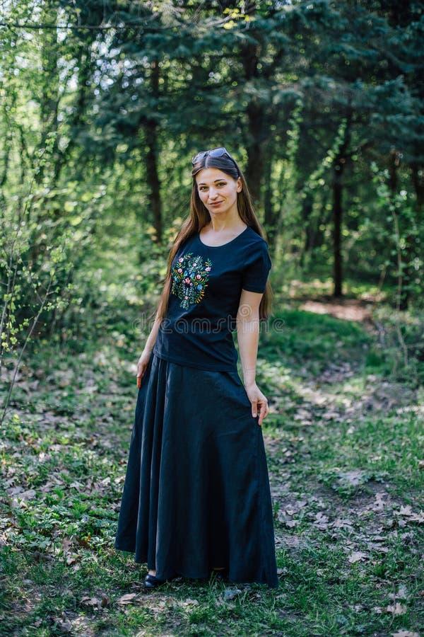 La ragazza in vestito nero lungo con ricamo cammina attraverso il legno fotografie stock
