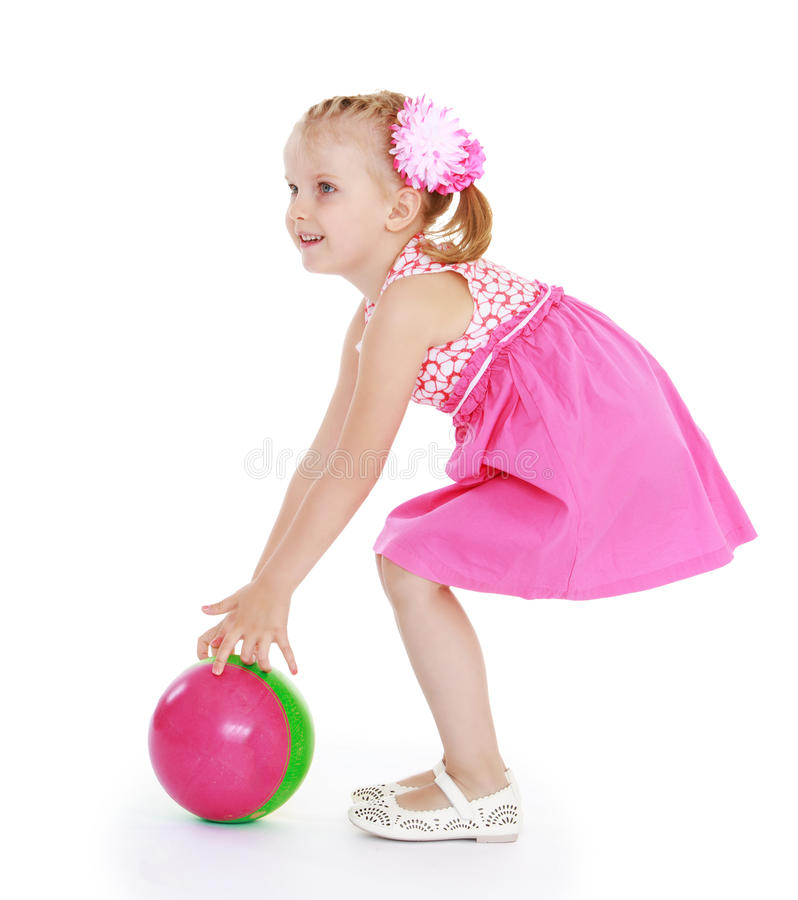 La ragazza in vestito rosa gioca con una palla fotografie stock libere da diritti