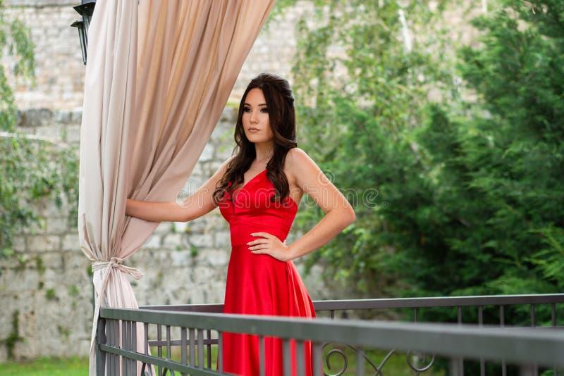 La ragazza in vestito rosso che posa e tiene una mano sulle anche dietro il recinto sul balcone e le tende nel giardino del risto immagini stock libere da diritti