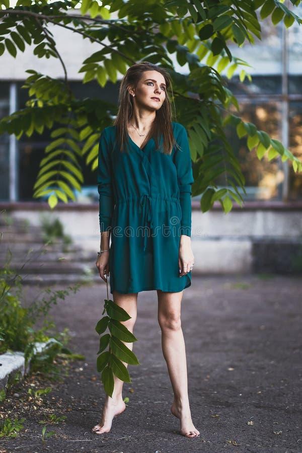 La ragazza in vestito verde sta a piedi nudi sulla via immagini stock