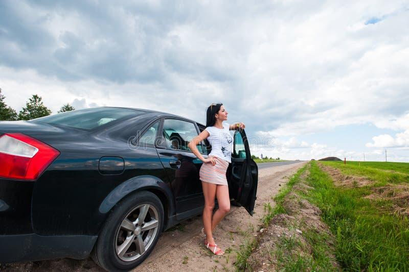 La ragazza vicino all'automobile ammira la natura Una donna vicino all'automobile ammira la natura immagine stock libera da diritti