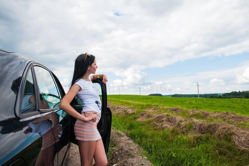 La ragazza vicino all'automobile ammira la natura Una donna vicino all'automobile ammira la natura immagine stock