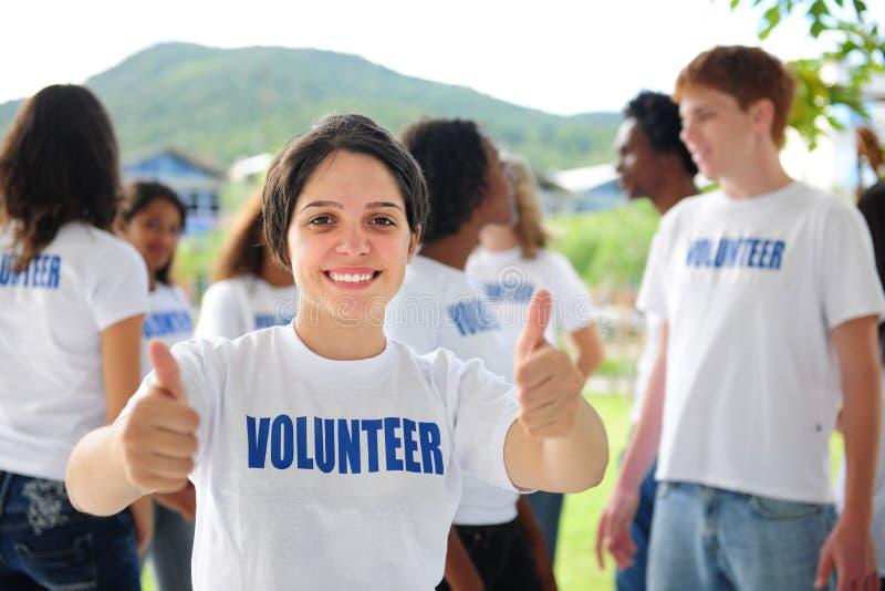 La ragazza volontaria felice che mostra i pollici aumenta il segno fotografia stock libera da diritti