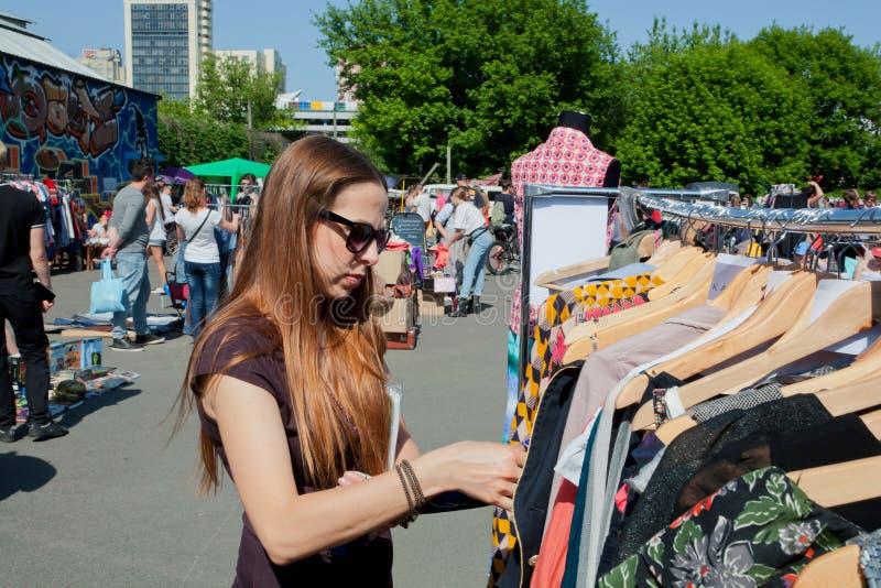 La ragazza vuole comprare il vestito sul mercato delle pulci della via immagini stock libere da diritti