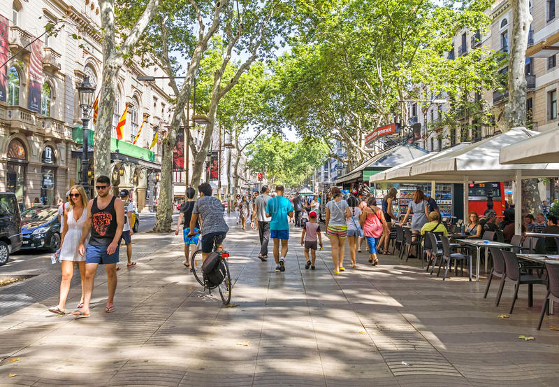 La Rambla in Barcelona, Spain. BARCELONA, SPAIN - JULY 6, 2015: Hundreds of people promenading in the busiest street of Barcelona, the Ramblas. The street stock images